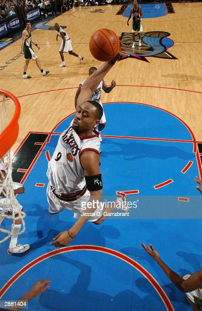 Kenny Thomas of the Philadelphia 76ers heads up for a dunk against the defense of the Seattle Supersonics January 19 2004 at the Wachovia Center in...