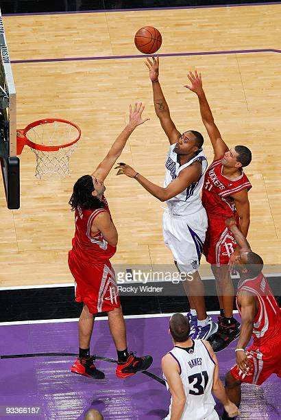 Kenny Thomas of the Sacramento Kings lays up a shot against Luis Scola and Shane Battier of the Houston Rockets during the game on November 13 2009...