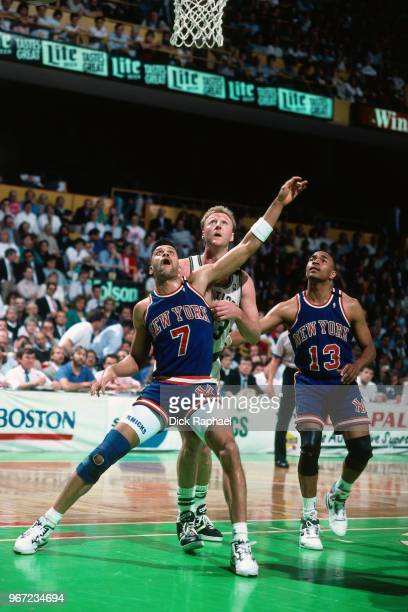Kenny Walker of the New York Knicks boxes out Larry Bird of the Boston Celtics circa 1990 at the Boston Garden in Boston Massachusetts NOTE TO USER...
