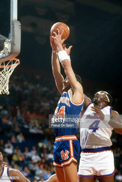 Kenny Walker of the New York Knicks grabs a rebound over Moses Malone of the Washington Bullets during an NBA basketball game circa 1988 at the...