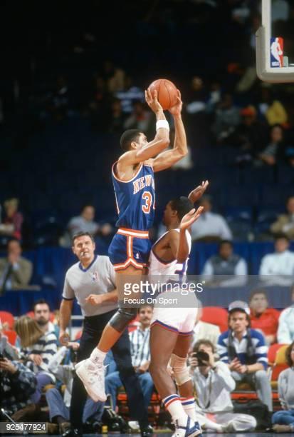 Kenny Walker of the New York Knicks shoots over Bernard King of the Washington Bullets during an NBA basketball game circa 1989 at the Capital Centre...