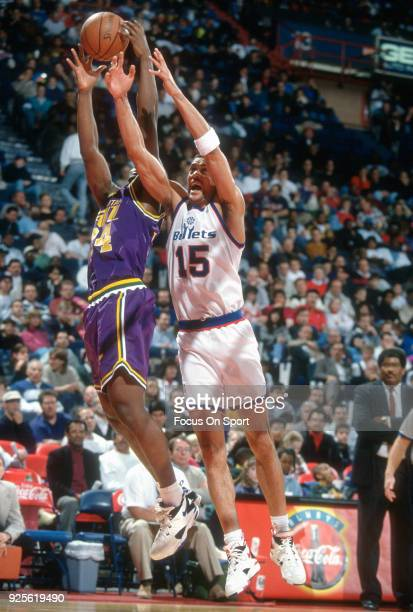 Kenny Walker of the Washington Bullets battles for a rebound with Bryon Russell of the Utah Jazz during an NBA basketball game circa 1993 at the US...