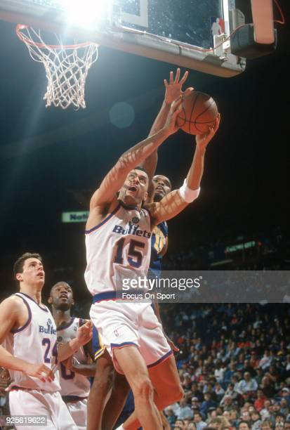 Kenny Walker of the Washington Bullets looks to get his shot over over the out stretched arm of Latrell Sprewell of the Golden State Warriors during...