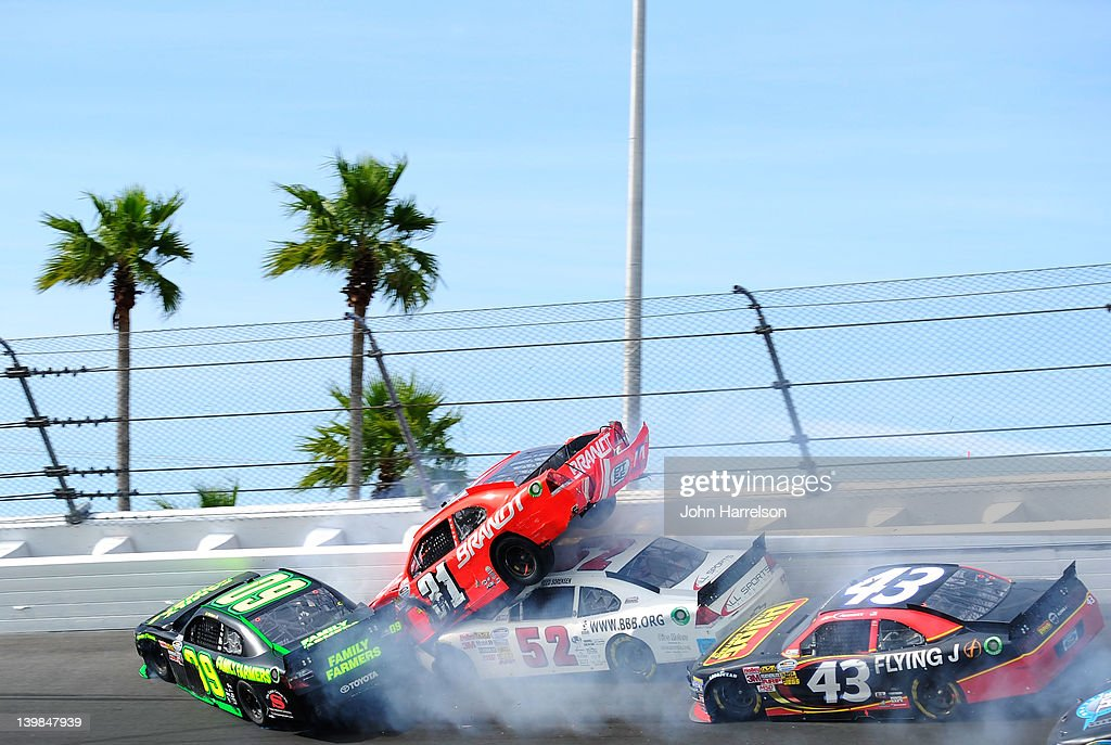 Kenny Wallace, driver of the #09 Family Farmers Toyota, spins into Justin Allgaier, driver of the #31 Brandt Chevrolet, who is lifted into the air by Reed Sorenson, driver of the #52 Means Racing Chevrolet, as Michael Annett, driver of the #43 Pilot Flying J Ford, tries to avoid the wreckage during the NASCAR Nationwide Series DRIVE4COPD 300 at Daytona International Speedway on February 25, 2012 in Daytona Beach, Florida.