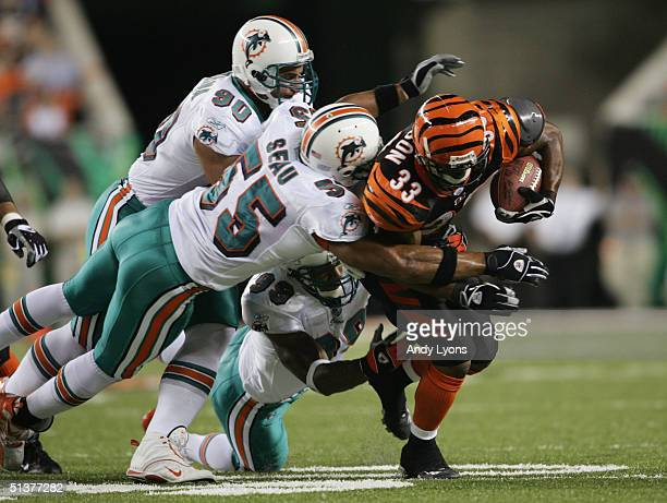 Kenny Watson of the Cincinnati Bengals runs with the ball against Junior Seau and Jason Taylor of the Miami Dolphins on September 19, 2004 at Paul...