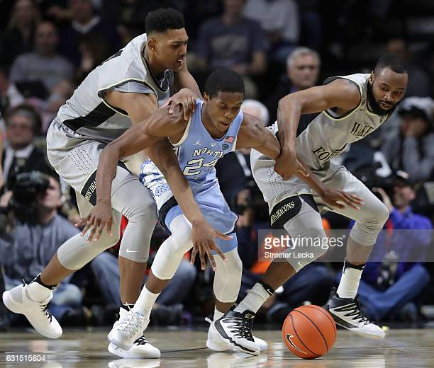 Kenny Williams of the North Carolina Tar Heels scrambles for a loose ball against teammates Doral Moore and Keyshawn Woods of the Wake Forest Demon...