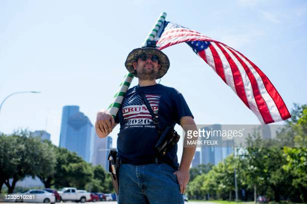 """Kenny Wolfam open carries a pistol and wears a """"Trump 2020"""" t-shirt while counter-protesting a """"Moms Demand Action"""" protest in response to a new..."""