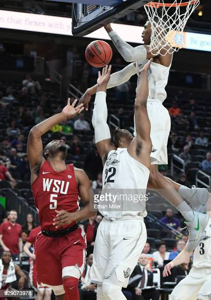 Kenny Wooten of the Oregon Ducks blocks a shot by Milan Acquaah of the Washington State Cougars as MiKyle McIntosh of the Ducks defends as time...