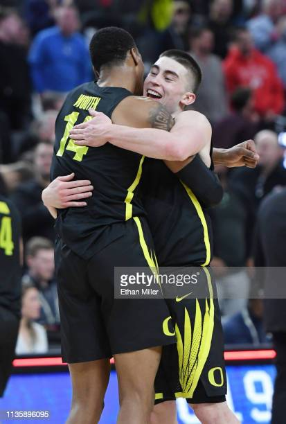 Kenny Wooten and Payton Pritchard of the Oregon Ducks celebrate on the court after their 6654 victory over the Utah Utes in a quarterfinal game of...