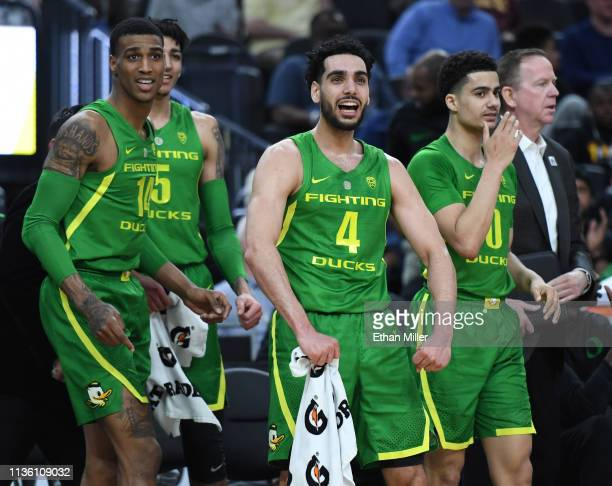 Kenny Wooten Miles Norris Ehab Amin and Victor Bailey Jr #10 of the Oregon Ducks react on the bench after a teammate got an offensive charge called...