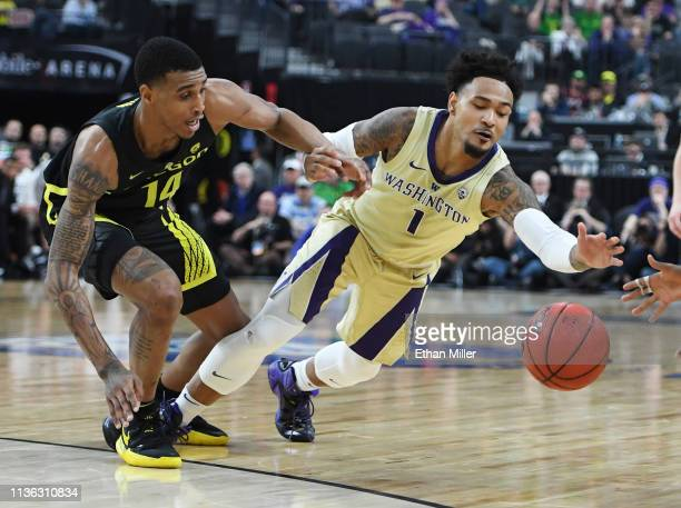 Kenny Wooten of the Oregon Ducks and David Crisp of the Washington Huskies go after a loose ball during the championship game of the Pac12 basketball...