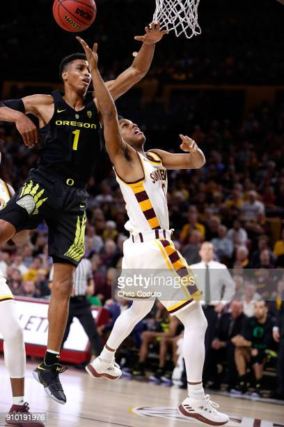 Kenny Wooten of the Oregon Ducks defends Tra Holder of the Arizona State Sun Devils during the first half of the college basketball game at Wells...