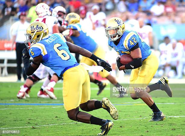 Kenny Young of the UCLA Bruins returns his interception as he looks for a block from Adarius Pickett during the first quarter against the Stanford...