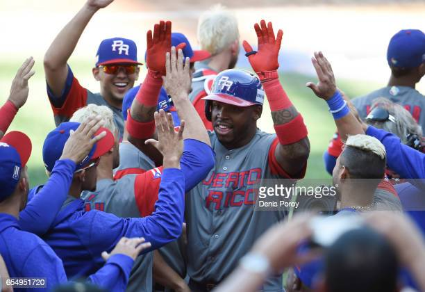 Kennys Vargas of Puerto Rico, center, is congratulated after hitting a two run home run during the ninth inning of the World Baseball Classic Pool F...