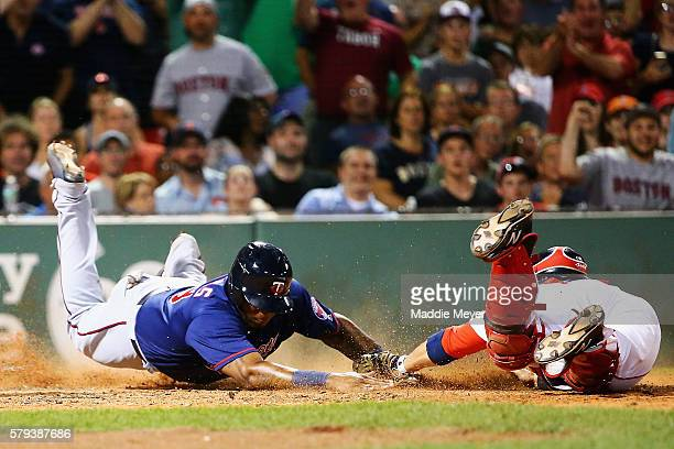 Kennys Vargas of the Minnesota Twins slides safely into home past Sandy Leon of the Boston Red Sox during the seventh inning at Fenway Park on July...