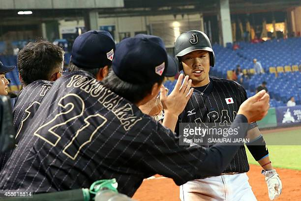 Kensuke Kondo of Japan celebrates with teammates after scoring in the top of the fifth during the IBAF 21U Baseball World Cup Group B game between...