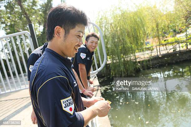 Kensuke Kondo of Japan throws food into a pond to feed fishes during a training session at Taichung Baseball Stadium on November 10 2014 in Taichung...