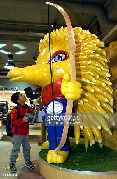 """Kensuke Tashiro of Japan admires a giant model of """"Millie"""" the echidna while shopping at the official Olympic merchandise store in Sydney 10 August..."""