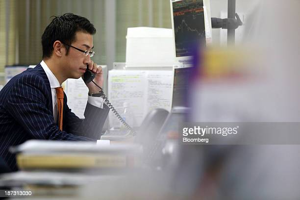 Kensuke Ueda a retail broker at Nomura Holdings Inc makes a phone call at his desk in a Nomura Securities branch office in Tokyo Japan on Friday Nov...
