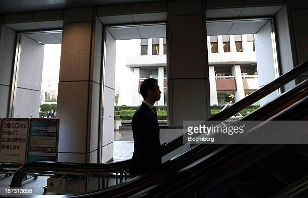 Kensuke Ueda a retail broker at Nomura Holdings Inc rides on an escalator in Tokyo Japan on Friday Nov 1 2013 For Ueda and his peers at firms...