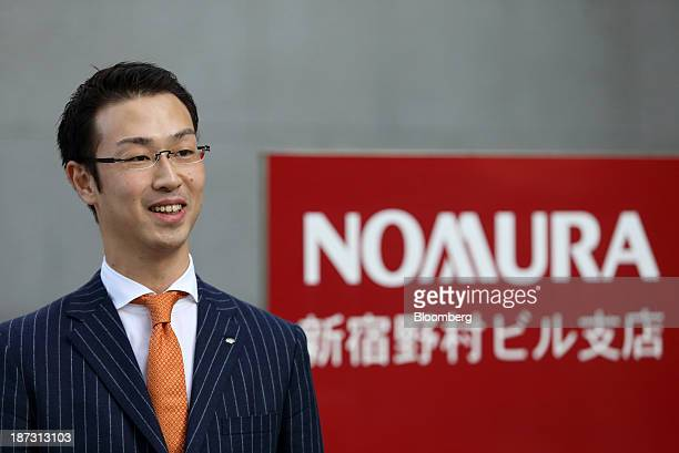 Kensuke Ueda a retail broker at Nomura Holdings Inc speaks outside a building housing his office in Tokyo Japan on Friday Nov 1 2013 For Ueda and his...