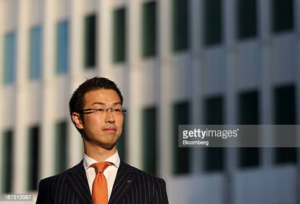 Kensuke Ueda a retail broker at Nomura Holdings Inc stands in front of a building housing his office in Tokyo Japan on Friday Nov 1 2013 For Ueda and...