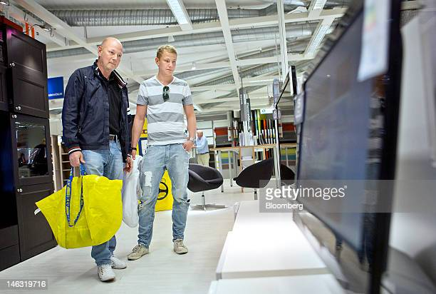 Kent Backman left and his son Robert look at 'Uppleva' television sets manufactured by Ikea AB as they sit displayed amongst other Ikea products...