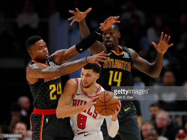 Kent Bazemore and Dewayne Dedmon of the Atlanta Hawks defend against Zach LaVine of the Chicago Bulls at State Farm Arena on October 27 2018 in...