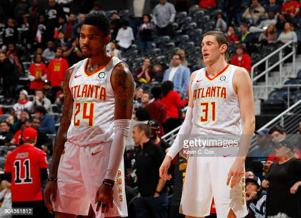 Kent Bazemore and Mike Muscala of the Atlanta Hawks react after Bazemore committed a foul on an offensive free throw rebound by Spencer Dinwiddie of...