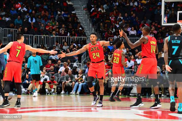 Kent Bazemore highfives Jeremy Lin and Dewayne Dedmon of the Atlanta Hawks during a game against the Charlotte Hornets on November 25 2018 at State...