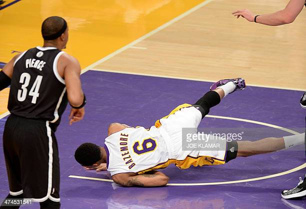 Kent Bazemore of Lakers falls down while blocking Xaviwer Henry during the game between the Los Angeles Lakers and Brooklyn Nets at Staples Center on...