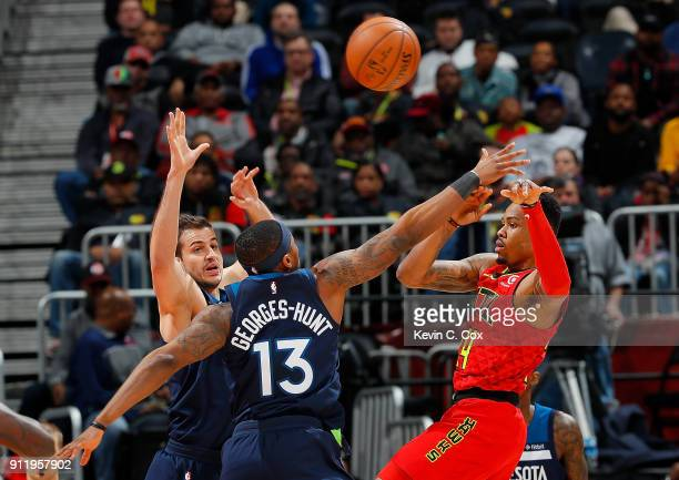 Kent Bazemore of the Atlanta Hawks passes the ball against Nemanja Bjelica and Marcus GeorgesHunt of the Minnesota Timberwolves at Philips Arena on...