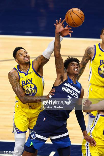 Kent Bazemore of the Golden State Warriors and Jaden McDaniels of the Minnesota Timberwolves battle for the ball during the third quarter at Target...