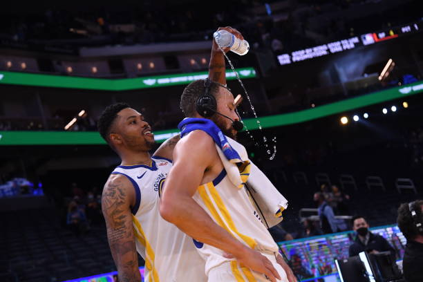 Kent Bazemore of the Golden State Warriors pours water on teammate Stephen Curry after the game against the Memphis Grizzlies on May 16, 2021 at...