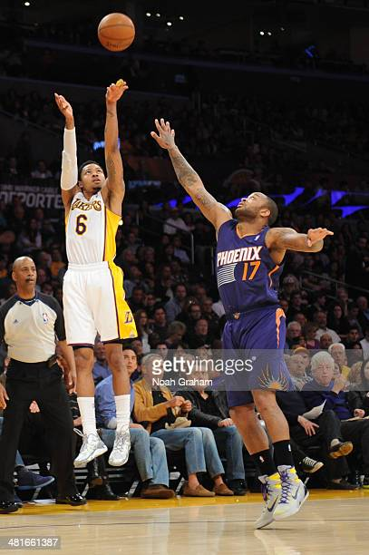 Kent Bazemore of the Los Angeles Lakers shoots against PJ Tucker of the Phoenix Suns at STAPLES Center on March 30 2014 in Los Angeles California...