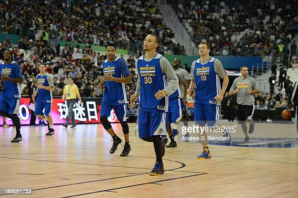 Kent Bazemore Stephen Curry and David Lee of the Golden State Warriors warms up during Fan Appreciation Day as part of the 2013 Global Games on...