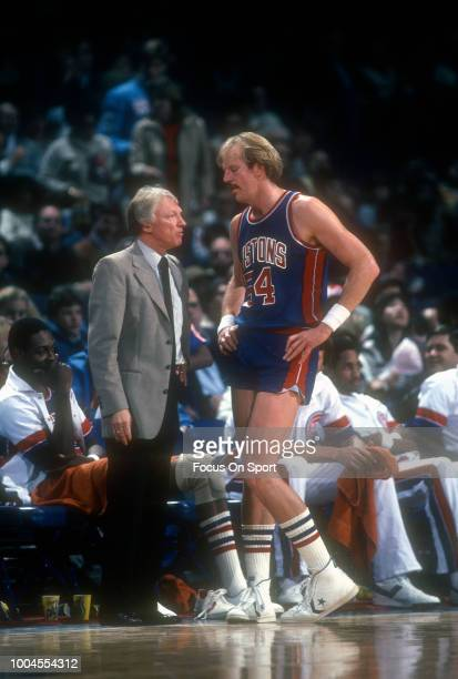 Kent Benson of the Detroit Pistons talks with coach Scotty Robertson against the Washington Bullets during an NBA basketball game circa 1982 at the...