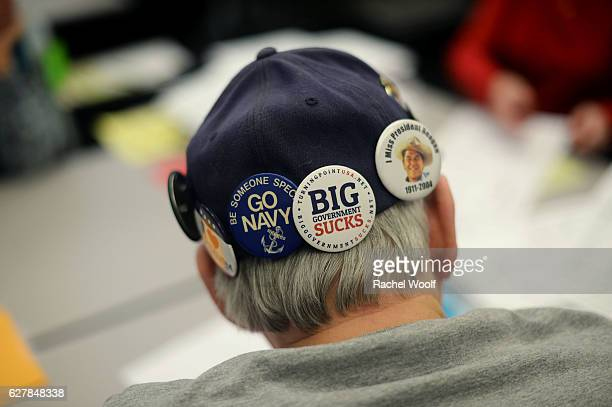 Kent Clarke a Precinct Delegate for the Republican Party wears a hat donned with buttons as he recounts presidential ballots at the Oakland Schools...