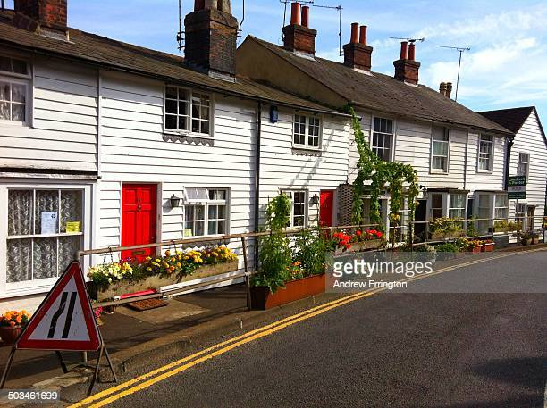 UK Kent Cranbrook terrace of old weatherboard houses with flowers and climbing shrubs extending onto pavement