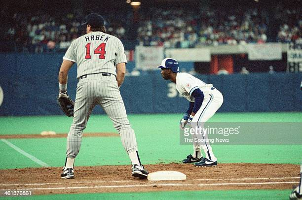 Kent Hrbek of the Minnesota Twins holds Devon White of the Toronto Blue Jays on first base during the 1991 American League Championship Series at...