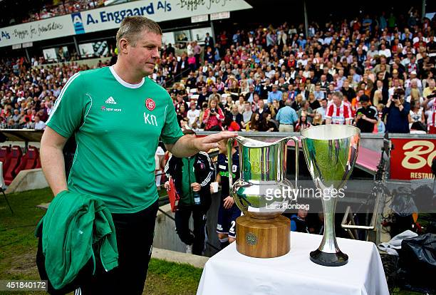 Kent Nielsen head coach of AaB Aalborg touches the Superliga trophy and the DBU Pokalen trophy prior to the Danish Superliga match between AaB...