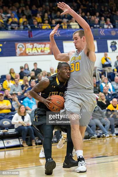 Kent State Golden Flashes G Deon Edwin is defended by Toledo Rockets F/C Luke Knapke during the second half of the NCAA Men's Basketball game between...