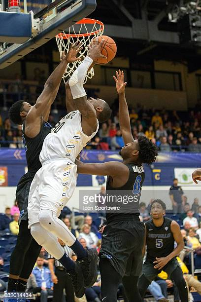 Kent State Golden Flashes G Deon Edwin shoots as Buffalo Bulls G Dontay Caruthers aqnd Buffalo Bulls W Blake Hamilton defend during the second half...