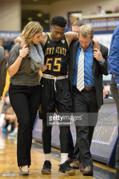 Kent State Golden Flashes G Kevin Zabo is helped from the court by trainers after injuring his ankle during overtime of the men's college basketball...