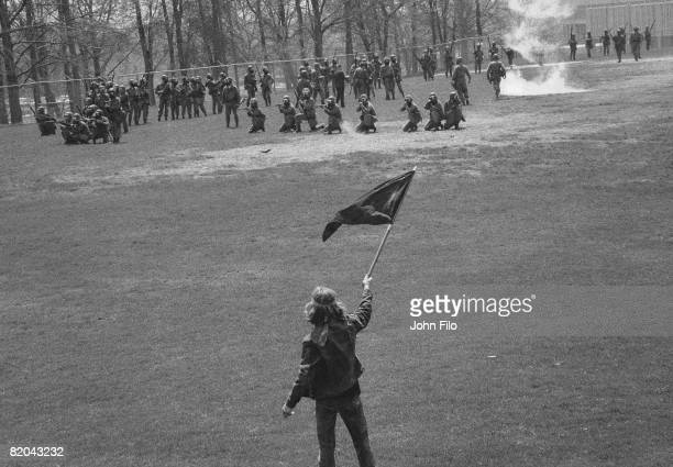 Kent State University student Alan Canfora waves a black flag as Ohio Army National Guardsmen kneel and aim their rifles on the university's practice...