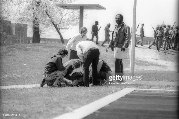 Kent State University students and others kneel on the grass beside their classmate Joseph Lewis after the latter had been shot when the Ohio...