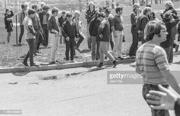 Kent State University students look at Jeffrey Miller's blood on the ground after the Ohio National Guard opened fire on antiwar protesters at Kent...