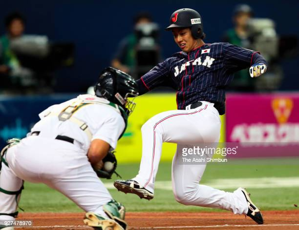 Kenta Imamiya of Japan slides safely into the homebase to score a run after a sacrifice fly by Go Matsumoto in the top of second inning during the...