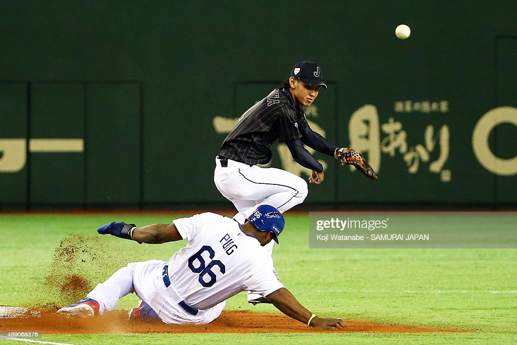 Kenta Imamiya #2 of Samurai Japan throws to first base to complete the double play while Yasiel Puig #66 of the Los Angeles Dodgers slides in in the fifth inning during the game four of Samurai Japan and MLB All Stars at Tokyo Dome on November 16, 2014 in Tokyo, Japan.