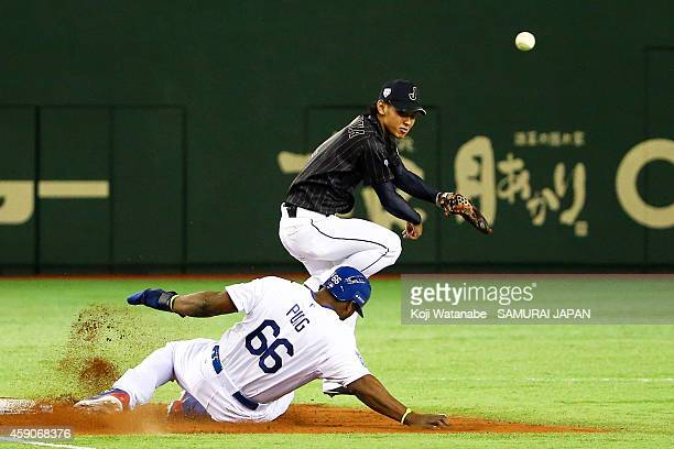 Kenta Imamiya of Samurai Japan throws to first base to complete the double play while Yasiel Puig of the Los Angeles Dodgers slides in in the fifth...
